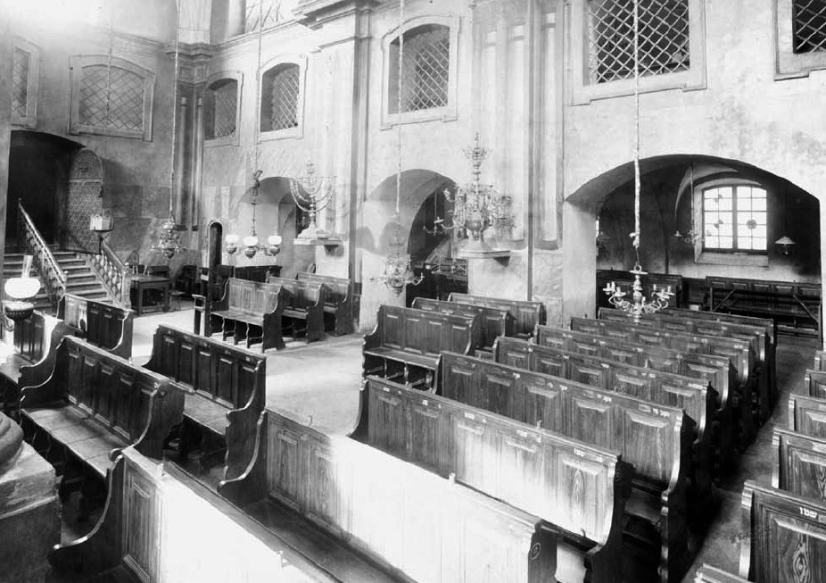 The interior of the Great Synagogue, behind the Bimah. Note steps down from entrance to the floor of the syangogue. Womens gallery at top and back.